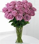 18 Lavender roses arranged in a clear glass vase with greens
