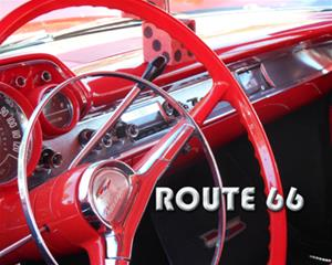 1957 Bel Air vintage car's red interior, with steering wheel, dashboard and fuzzy dice, that says 'Route 66' in chrome letters
