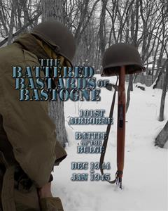 WWII American airborne soldier kneeling by a field memorial of a helmet and rifle in the snow that says 'Battered Bastards of Bastogne'