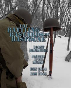 WWII American airborne soldier kneeling by a field memorial of a helmet and rifle in the snow that says 'Battling Bastards of Bastogne'