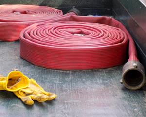 Red fire hose coils rest in a truck bed with a pair of yellow work gloves