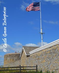 Historic Fort Snelling exterior wall with American flag and wooden fence with blue sky in the background