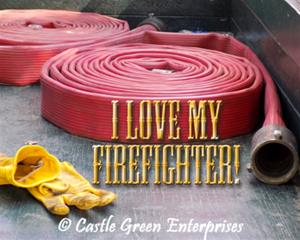 Red fire hose coils rest in a truck bed with a pair of yellow work gloves and gold letters that say 'I love my firefighter'