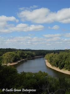 The Mississippi River with green trees along its banks, the distant Minneapolis skyline, and blue sky above