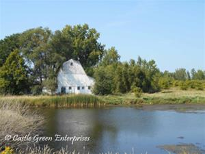 A white barn sits among green trees behind a blue pond