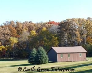 A brown pole barn sits in a green field with colorful autumn trees in the background