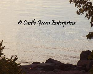 Dark angled rocks and green trees sit on a pebbly beach in front of purple water