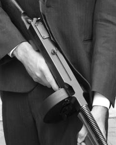 A man wearing a dark pinstriped suit holds a Thompson submachine gun