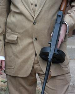 A man in a tan suit and vest holds a Thompson submachine gun