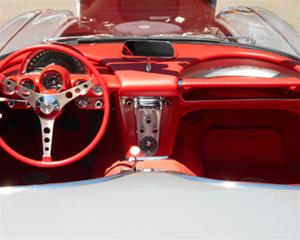 A white Corvette convertible's driver and passenger seats and red interior are visible