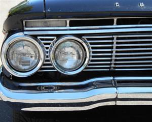 1961 black vintage car's round double headlights in a chrome grille