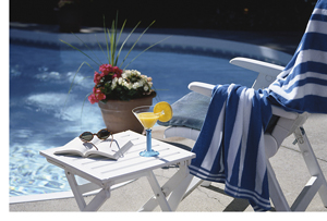 Poolside chair with book, glasses, and drink on a table